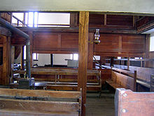 A room with wooden benches and paneled wood and plaster walls with an iron stove in the middle. An exhaust pipe leads out from the stove to the left. There is an oil lamp on a post in the middle of the picture.
