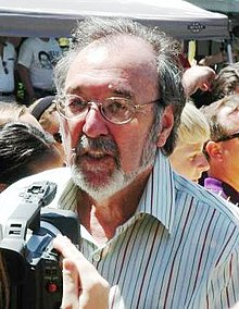 A video camera is being pointed at a bearded man who is wearing glasses. Some other people stand in the background.