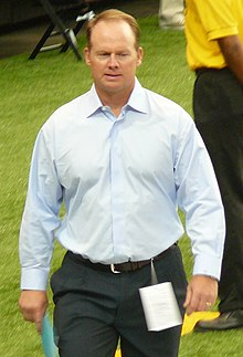 Candid photograph of Ireland walking on a football sideline wearing grey slacks and a light blue button-up shirt and holding a piece of paper in his right hand