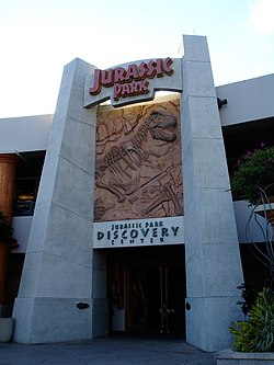 """The gateway to a facility reading """"Jurassic Park"""" at the top, """"Discovery Center"""" at the bottom, and a rocky panel with a Tyrannosaurus skeleton in-between."""
