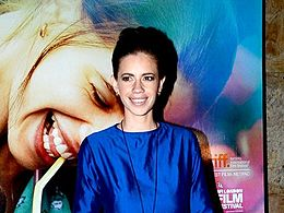 Koechlin smiling at the camera in blue dress