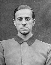 Photo noir et blanc (format photo d'identité, en buste, de face) de Karl Brandt, médecin SS de Hitler. L'homme porte une veste claire au col foncé fermé.