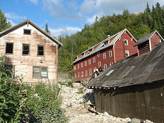 Kennecott, Alaska - The Kennecott hospital (left) stood out as the town's only white-washed building. The vast majority of other town structures, including workers' bunkhouses (right), were painted red, the least expensive color at the time. The Kennecott hospital was also the site of the first X-ray machine in Alaska.