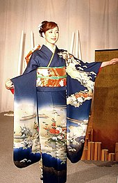 A young woman stood up in a dark blue long-sleeved kimono with a white designs across the lap and the middle of the sleeves. The sash she wears is orange with a thin green belt in the centre