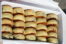 24 buns in golden brown are put in a white rectangular box. The buns are arranged like an abacus.