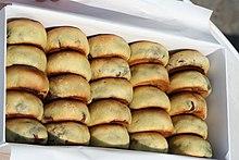 24 panini dorati sono messi in una scatola rettangolare bianca.  I panini sono disposti come un abaco.