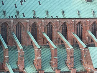 Flying buttress - Arching above a side aisle roof, flying buttresses support the main vault of St. Mary's Church, in Lübeck, Germany.