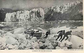 Six men pulling a boat onto an icy shore, with a line of ice cliffs in the background