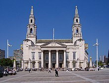 A pedestrian square in sunny weather. At the rear is a large neo-Georgian building of Portland stone. It has a giant portico with four Corinthian columns and a pediment. On the ground floor, there are three entrance doors under the portico and two windows on either side of it. All the doors and windows have Gibbs surrounds and pediments. The window pediments are normal, while those over the doors are segmental. The first floor has seven plain windows, three of them behind the portico, and all of them larger than those on the ground floor. On either side of the building are two tall towers in Wren style with elaborate columned pavilions surmounted by smaller pedimented ones, and on top of each is an obelisk surmounted by a golden owl. In front of the building on each side there are similar obelisks and owls, and prominent gold clocks are attached to the sides of the building at second-floor level. In the background on both sides are tall modern buildings.