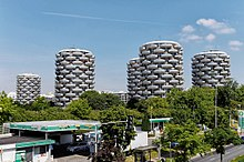 Five of the building towers, with trees in the foreground and a petrol garage