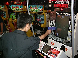 Arcade game - A player in Japan playing Police 911, an arcade game in which players use a light gun.