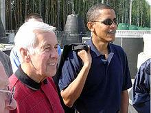 Homem de cabelos grisalhos e Obama estão de pé, vestindo camisas pólo casuais.  Obama usa óculos escuros e segura algo pendurado no ombro direito.