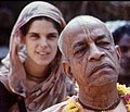 A color photo of a young Western woman dressed in sari and an Indian Swami in the forefront