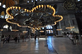 The stone floor of Hagia Sophia dates from the 6th century. Massive central chandelier and two of the medallions - Hagia Sophia (8394693292).jpg