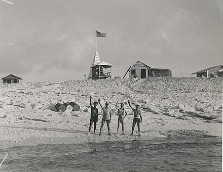 Four people wave goodbye before they begin their shifts as colonists. Men left at Jarvis Island (80-CF-798677-14).jpg