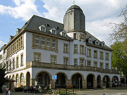 """Unter Denkmalschutz stehendes """"Altes Rathaus"""" (1912) mit Mittelturm und Laubengang mit Rundbögen in Menden (Sauerland)."""