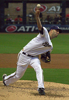 "A man wearing a white baseball uniform with ""Brewers"" written across the chest stands on the pitcher's mound having just thrown a ball with his right hand"