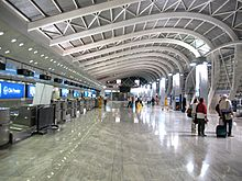 A hall with curved ceiling inside an airport. Indicators, blue screens and counters on the left side