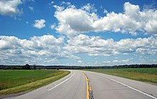 A paved two-lane road curving to the left into the distance through a large grassy area below a blue sky filled with cumulus clouds