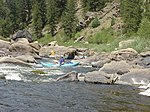 Canoers run rapids on a boulder-strewn river in the mountains.