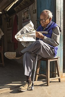 Photograph of a bespectacled man sitting on a stool with his legs crossed reading a newspaper in the morning