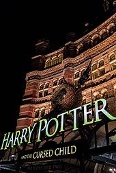 Vue sur la façade d'un bâtiment rouge éclairé de nuit. Au-dessus de l'entrée du bâtiment est placé un décor comportant un nid avec deux ailes et au-dessous duquel se trouve écrit en grosses lettres jaunes «Harry Potter and the Cursed Child»