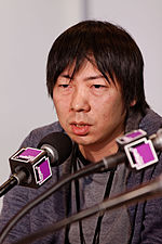 A photo of a middle aged Japanese man who is surrounded by microphones.