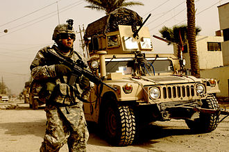 A U.S. soldier on patrol with the support of a Humvee vehicle Patrol in Iraq, March 2008.jpg