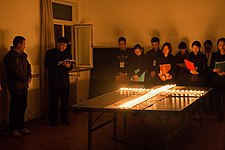 People praying at a candle cross.JPG