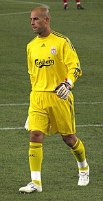 Pepe Reina wearing a yellow long-sleeved goalkeeper's shirt with the Liverpool FC, Adidas and Carlsberg logos printed on the front, along with goalkeeper gloves, yellow shorts and socks, and white cleats.
