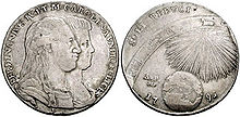 Two heads appear on a grey coin surrounded by Latin text