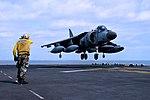 Plane handler directing AV-8B Harrier of the Italian Navy during landing on USS Bataan (LHD-5) 141009-N-JX484-068.jpg