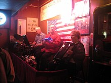 Three musicians, left to right: older man with white hair playing drums, middle-aged man looking into camera, older woman with white hair playing accordion. Walls are covered with an American flag and signs.