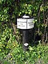 "A black post supports a plaque which says on the left ""Shardlow 92 miles"" and on the right ""Preston Brook""."