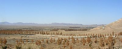 Sparse brown vegetation in dusty soil fills the foreground, fading to distant mountains along the horizon. A barely discernible scattering of buildings is in the middle-distance.