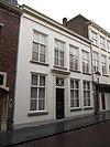foto van Huis met witgepleisterde lijstgevel en ingangspartij met geblokte pilasters en kroonlijstje met triglyphen