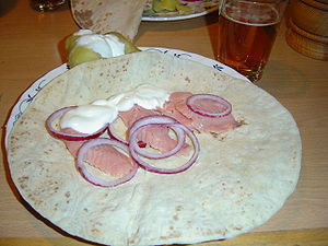 Lefse - A lefse topped with rakfisk served with onion and sour cream.