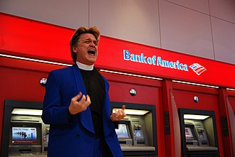 Reverend Billy and the Church of Stop Shopping - Reverend Billy attempting to exorcise bad loans and toxic assets from the Bank of America ATM in Union Square, New York City, 2009