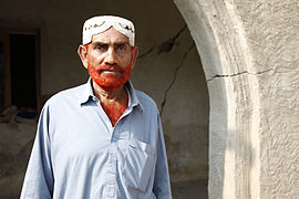 Roshan Ali, 60, stands in front of the remains of his flood-damaged home, in Pakistans Sindh Province (5330437377).jpg