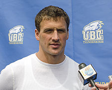 Photo is a profile head shot of Ryan Lochte, a 28-year-old white man with sandy brown hair and blue eyes, standing behind a microphone