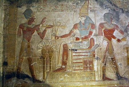 Seti I al cospetto del dio Horus, il cui capo di falco è sormontato dalla Doppia Corona dell'Alto e Basso Egitto. Tempio di Abido.
