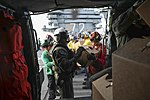 Sailors load boxes of water onto an MH-60R Sea Hawk. (37015526782).jpg