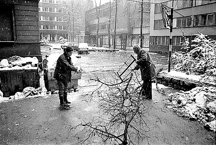 Besieged residents collect firewood in the bitter winter of 1992 during the Siege of Sarajevo. Sarajevo Siege firewood couple 1992.jpg