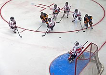 A hockey puck in midair over the ice between a group of five players in white jerseys and two in black at the top of the image, and a goalkeeper in white at the bottom