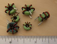 Several small toroidal inductors. The major scale is in inches.