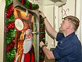 Sonar Technician (Surface) 3rd Class Matthew Wellington hangs holiday decorations.jpg