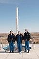 Soyuz TMA-11M crew in front of a Proton rocket statue.jpg