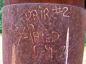 Construction of the Trans-Alaska Pipeline System - Graffiti written on a pipeline vertical support member indicates when a nearby weld was X-rayed by quality control inspectors.