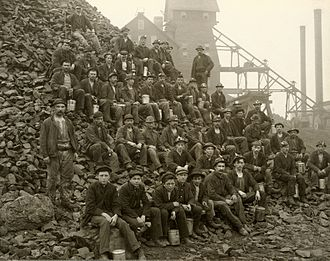 Copper Country - Miners pose with lunch pails in hand on a mine rock pile outside of the Tamarack mineshaft. This mine was one of the most productive mines in the Copper Country.