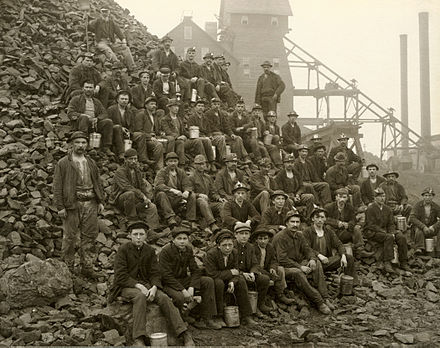 Miners at the Tamarack Mine in Copper Country, Michigan, U.S. in 1905. TamarackMiners CopperCountryMI sepia.jpg